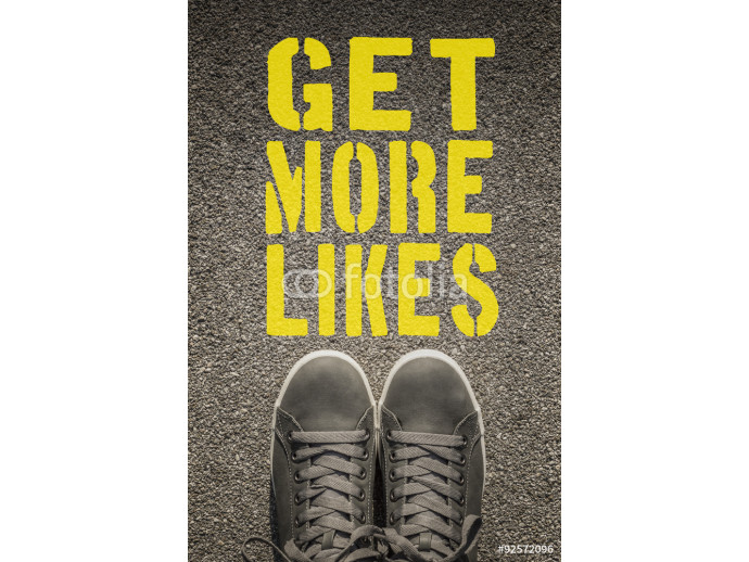Sneakers with Get More Likes written on the asphalt road 64238