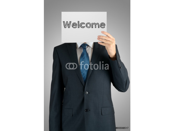 businessman holding a white sheet of paper with the inscription on grey background: welcome 64238