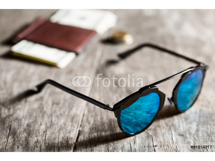 Stylish sunglasses with blue tinted mirror on textured wooden ba 64238