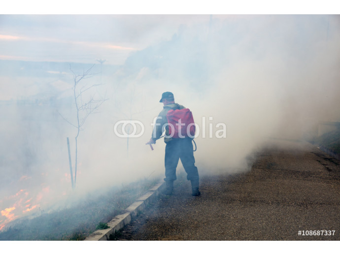 Firefighter extinguishes the fire of last year's dry plants 64238