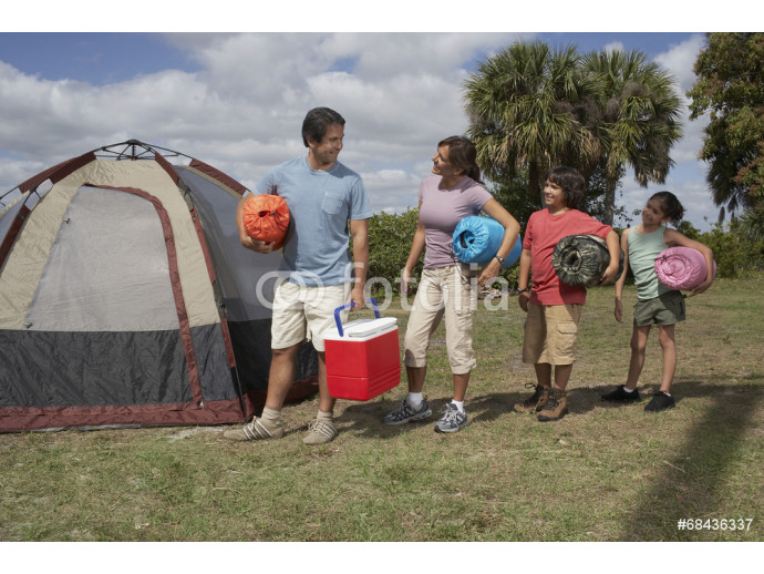 Hispanic family holding sleeping bags next to tent 64238