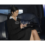 Businesswoman holding palm pilot in back seat of car 64238