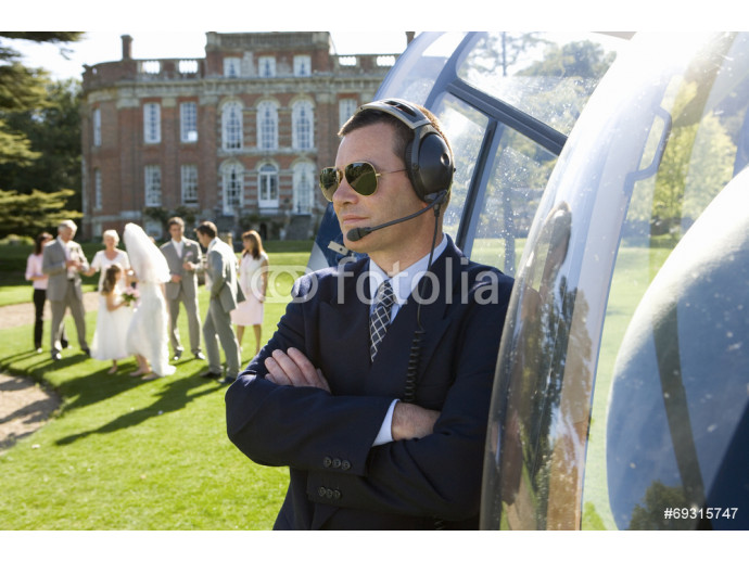 Helicopter pilot in sunglasses by helicopter, wedding party in background 64238