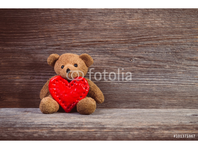 Teddy bear with heart sitting on old wood background. 64238