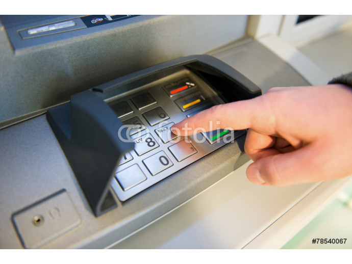 Close-up of hand entering PIN code on ATM machine keypad. 64238