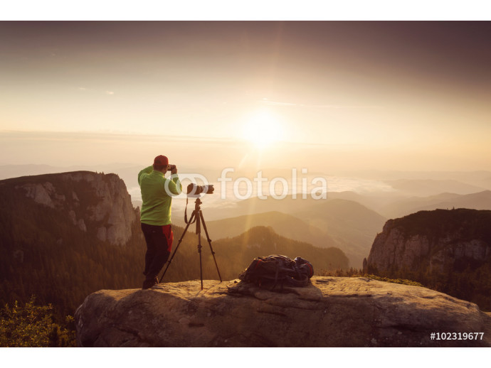 Photographer taking pictures at sunrise over mountains 64238