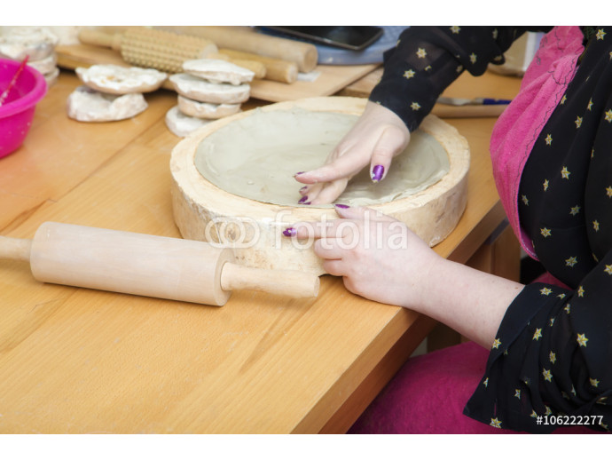 Woman's hands  making a white clay plate 64238