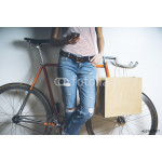 Hipster girl with vintage orange bicycle using modern smart phone, mock-up of blank paper shopping bag with handles 64238
