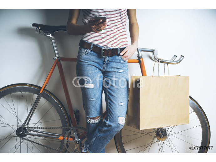 Fototapeta Hipster girl with vintage orange bicycle using modern smart phone, mock-up of blank paper shopping bag with handles 64238