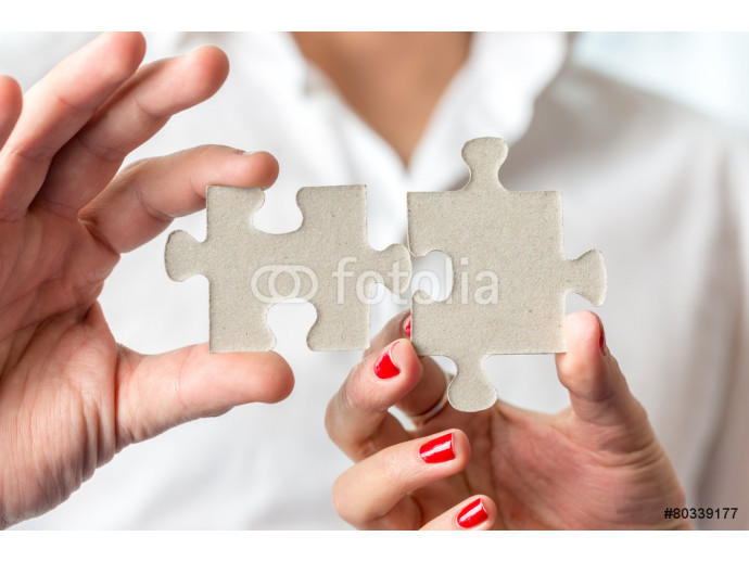 Teamwork concept using two puzzle pieces being fitted together b 64238