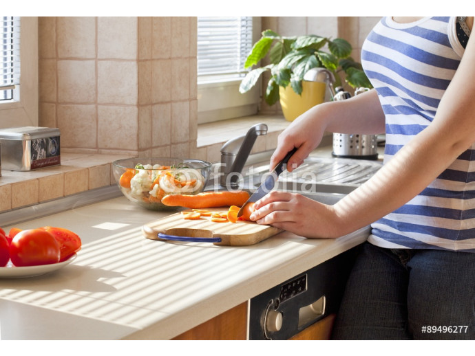 A woman cutting carrots 64238