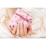 Hand with french manicured nails holding a gift box with bow 64238