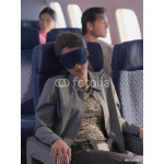 Young woman sleeping on airplane with eye mask 64238