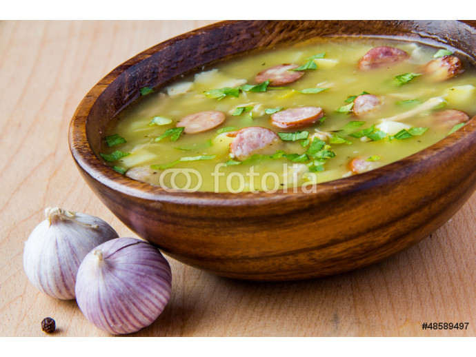 Pea soup with smoked sausages in a wooden plate 64238