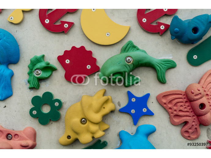 3D shapes and icons on a wall, some with climbing hand holds 64238
