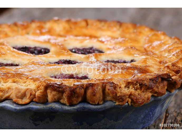 Whole blueberry pie on rustic wooden table 64238