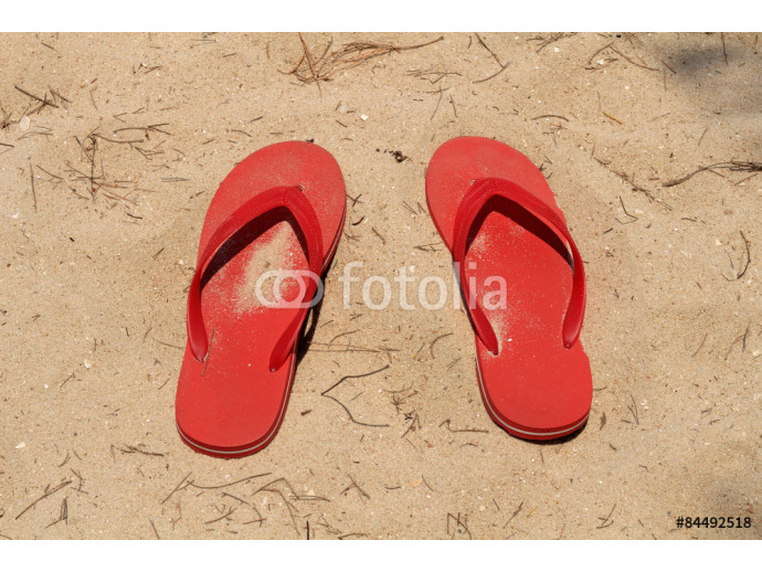 Pair of red slippers on the sand 64238