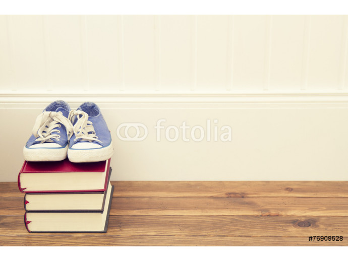 A pair of blue sneakers on a stack of books. 64238