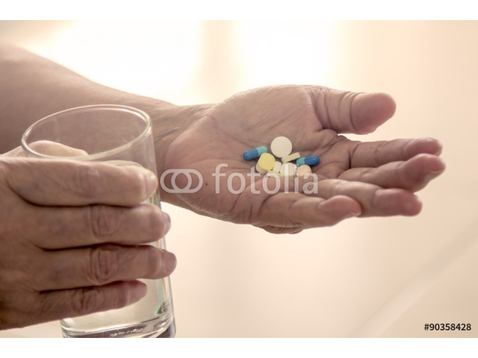 Old woman hand holding heap of pills and water glass in vintage 64238