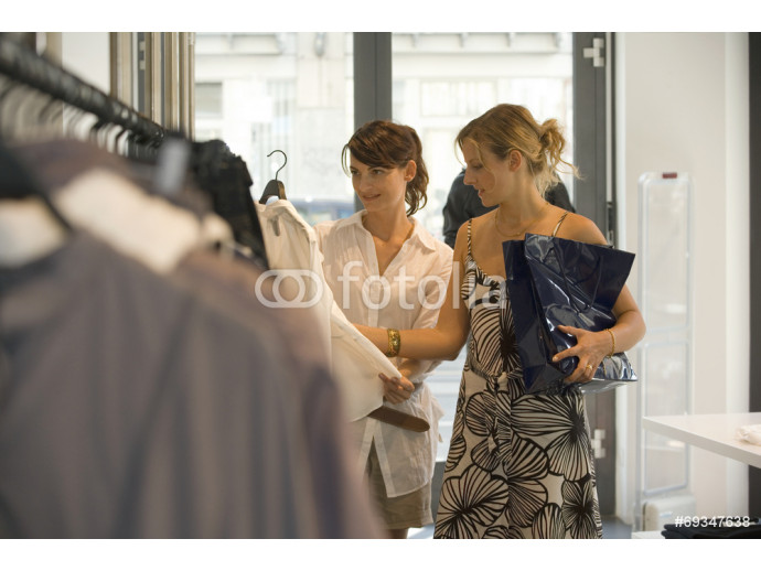Women looking at clothes on display at a boutique. 64238