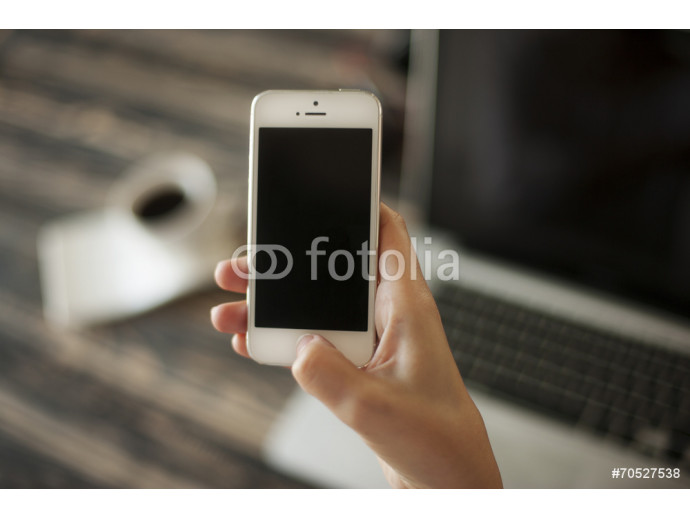 Woman hand holding mobile phone, and laptop and coffee cup in ba 64238