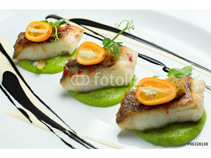Delicious fish served on white dish, decorated with salad and sauce 64238