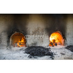 fire burning in a traditional oven underneath halwa cooking pans in Nizwa, Oman 64238