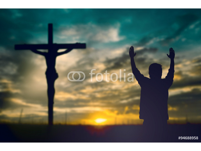 Silhouette of man with raised hands over blur cross concept for 64238