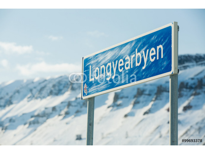Road sign of Longyearbyen. Beautiful white snowy landscape. Mountains and blue sky on the background. Sunny weather. Longyearbyen, Svalbard.