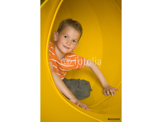 Portrait of a boy sitting in a tubular slide and grinning 64238