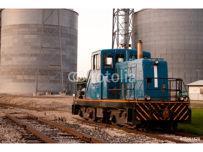 Train head car stopped on tracks in front of grain mill 64238
