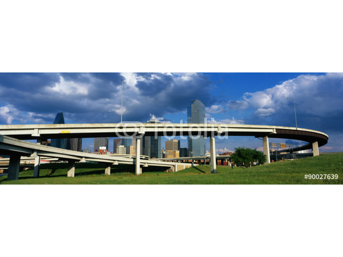 This is a freeway overpass with the Dallas skyline visible behind it. The freeway curves and snakes around in a circle in front of the city. 64238