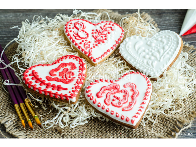 Gingerbread hearts painted red and white glaze, selective focus 64238