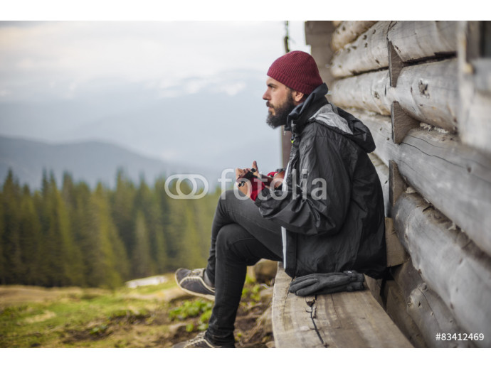 bearded guy playing guitar in mountains near wooden house 64238