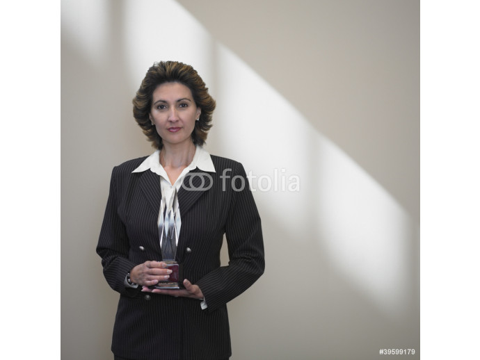 Businesswoman holding a glass trophy 64238