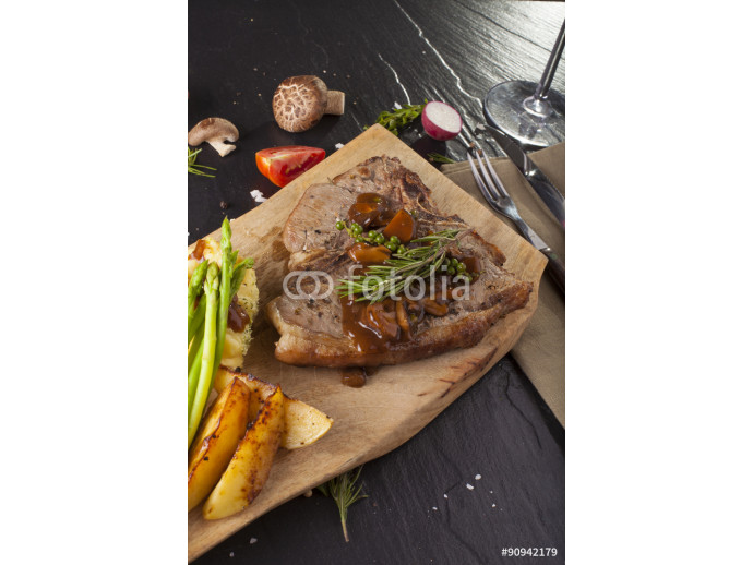 T-bone steak, a prepared piece of grilled T-bone steak brown sauce with mashed potato and vegetable on dining table decorated 64238
