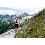 middle age man in sportswear running on trail in  high mountain scenery with peaks 64238