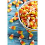 Halloween candy corns in bowl on blue wooden background 64239