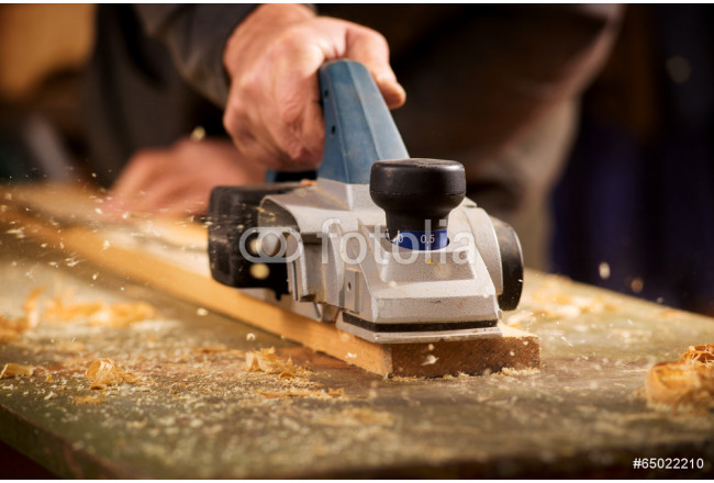 Elderly man planing a plank of wood 64239