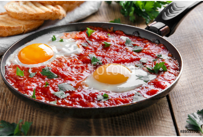 fried eggs in tomato sauce in the pan 64239