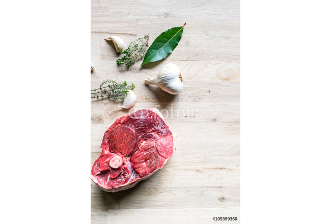 beautiful raw slice of an organic leg of lamb meat with garlic, fresh bay laurel and thyme on a natural oak tree cutting board seen from above 64239