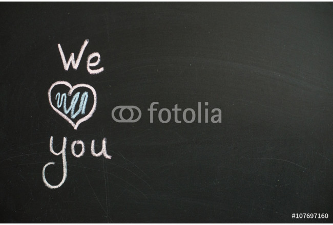 We Love You. Handwritten message on a chalkboard with an illustrated heart used as a symbol of love in this Valentines message. 64239