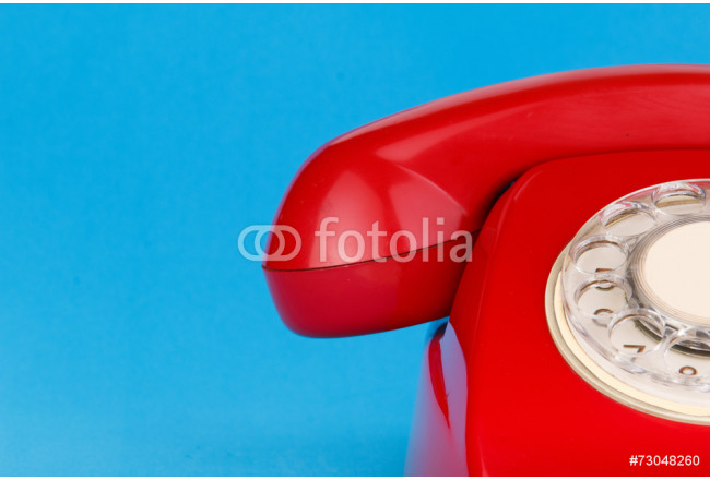 Red telephone hanging on blue background. 64239