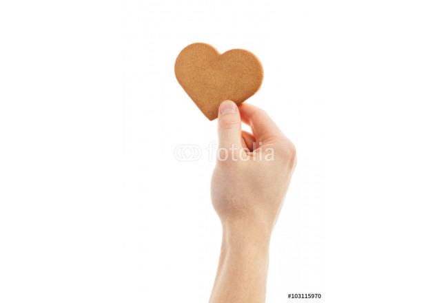 hand is holding a love shaped gingerbread cookie. 64239