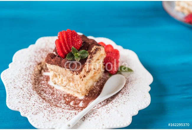 Piece of tiramisu cake with mint and strawberries on a blue background 64239
