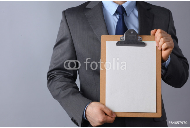 Young man standing with folder, isolated on gray background 64239