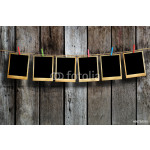 Old picture frame hanging on clothesline on wood background. 64239