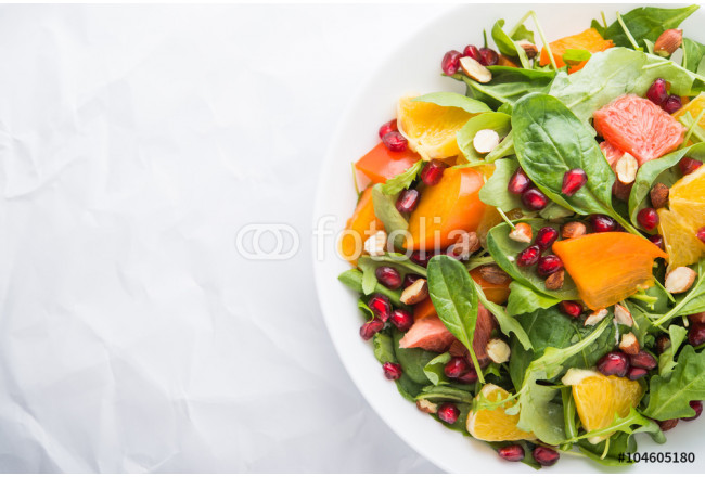 Fresh salad with fruits and greens on white background top view with space for text. Healthy food. 64239