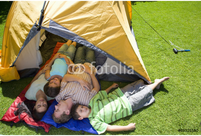 Bild auf Leinwand Family laying in tent on lawn 64239
