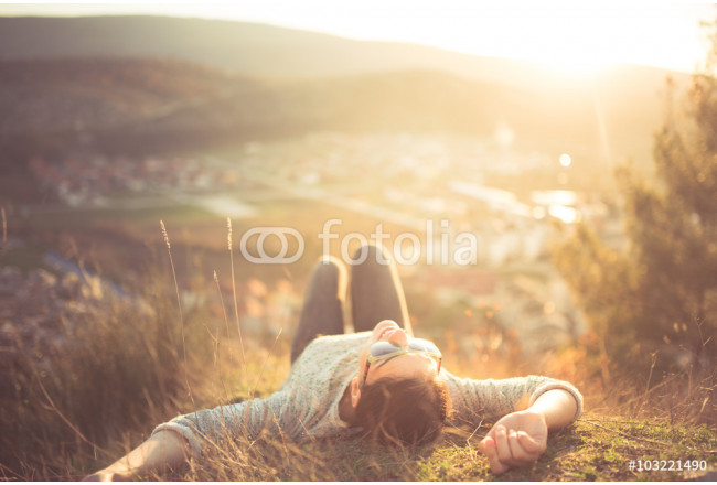 arefree happy woman lying on green grass meadow on top of mountain edge cliff enjoying sun on her face.Enjoying nature sunset.Freedom.Enjoyment.Relaxing in mountains at sunrise.Sunshine.Daydreaming 64239